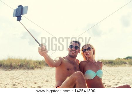 love, travel, tourism, technology and people concept - smiling couple on vacation in swimwear sitting on summer beach and taking picture with smartphone selfie stick