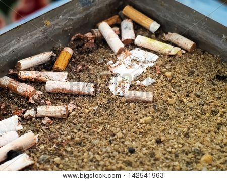 dirty metal public ash tray with cigarettes