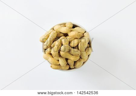 Bowl of raw unshelled peanuts