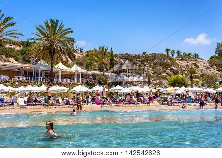 PAPHOS CYPRUS - JULY 24 2016: People relaxing on Coral Bay Beach one of the most famous beaches in Cyprus.