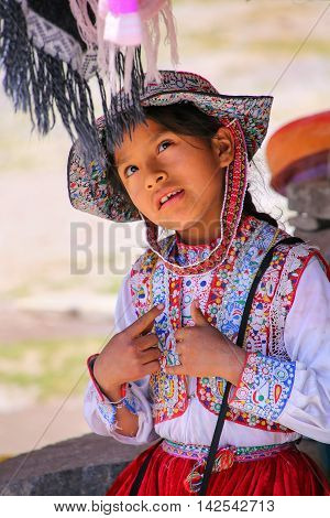 Maca, Peru-january 16: Unidentified Girl In Traditional Dress Sits At The Market On January 16, 2015
