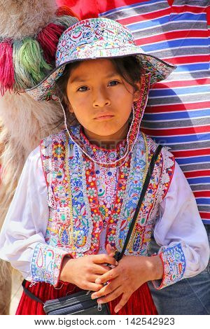 MACA PERU-JANUARY 16: Unidentified girl in traditional dress stands at the market on January 16 2015 in Maca Peru. Maca is one of the three main tourist towns of the Colca Canyon.