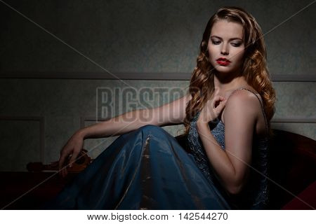 woman in blue dress 1940s portrait sitting on couch