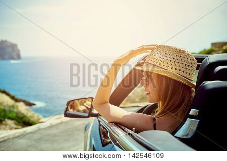 Beautiful blond smiling young woman with hat and sunglasses in convertible top automobile looking sideways while parked near ocean waterfront