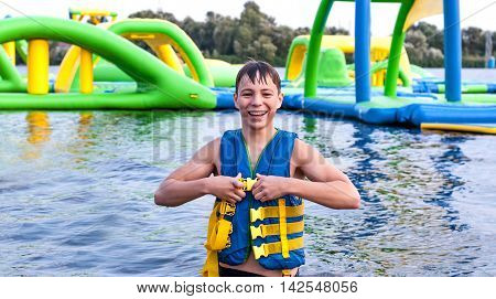 Happy teenager near a water slide in the lifejacket
