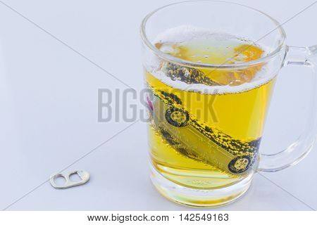 horizontal photo of toy car in a glass of beer isolated on white background. Drunk-driving Prevention Concept.