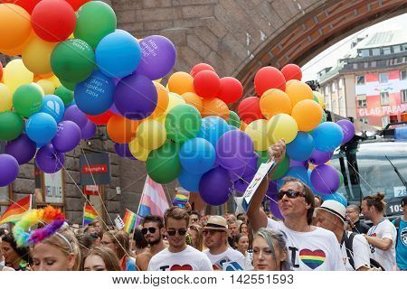 STOCKHOLM SWEDEN - JUL 30 2016: Happy people holding colorful balloons in red yelllow and blue in the Pride parade July 30 2016 in Stockholm Sweden