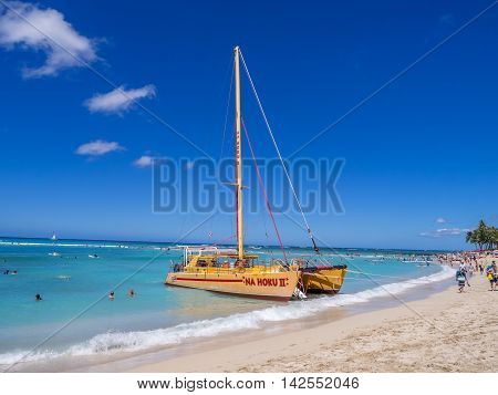 HONOLULU, HI - AUG 3: A catamaran waiting for tourists at Waikiki Beach on August 3, 2016 in Honolulu. Catamarans are a popular tourist activity at Waikiki Beach and offers a unique experience.