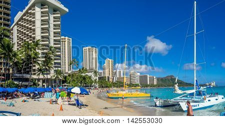 HONOLULU, HI - AUG 4: A catamaran waiting for tourists at Waikiki Beach on August 4, 2016 in Honolulu. Catamarans are a popular tourist activity at Waikiki Beach and offers a unique experience.