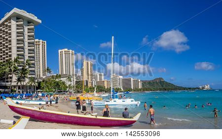HONOLULU, HI - AUG 4: Hawaiian canoes waiting for tourists at Waikiki Beach on August 4, 2016 in Honolulu. Canoes are a popular tourist activity at Waikiki Beach and offers a unique experience.