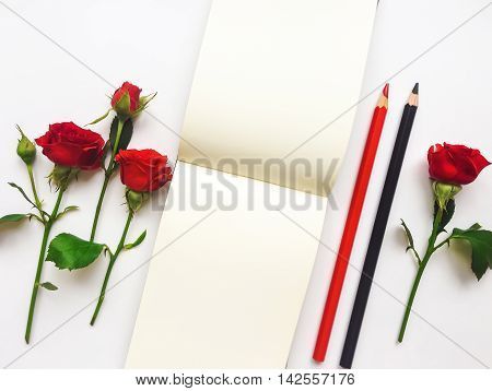 Colorful composition with sketchbook red roses and pencils. Flat lay on white table top view overhead view with copy space