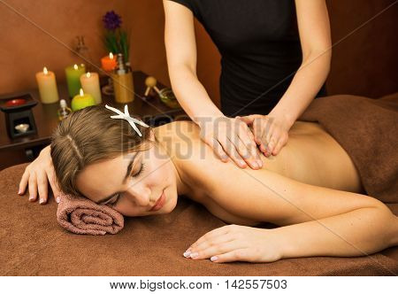 Attractive lying young woman in spa salon with hands of a masseur