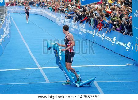 STOCKHOLM - JUL 02 2016: Triathlete Alistair Brownlee after winning the race his brother Jonathan in the background in the Men's ITU World Triathlon series event July 02 2016 in Stockholm Sweden