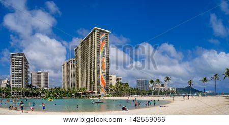 HONOLULU, USA - AUG 7: Sun lovers on Waikiki beach at the Hawaiian Hilton on August 7, 2016 in Honolulu, Usa. Waikiki beach is neighborhood of Honolulu, best known for white sand and surfing.