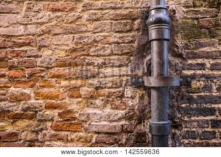 Old brick wall with drainpipe