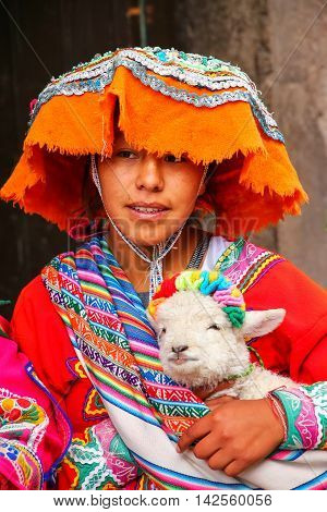 Cusco, Peru - January 20: Unidentified Young Woman In Traditional Dress Holds Lamb In The Street On