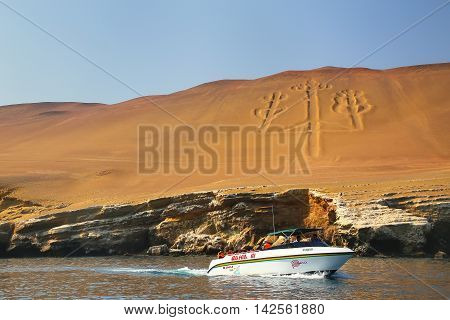 PARACAS PERU-JANUARY 26: Unidentified people look at Candelabra of the Andes from a boat on January 26 2015 in Pisco Bay Peru. Candelabra is a well-known prehistoric geoglyph found on the northern face of the Paracas Peninsula