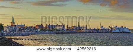 Panoramic view from the coastal road South of Elsinore. Image recorded across a stretch of water in the golden hour and features church towers train station Kronborg castle and ferry terminal.