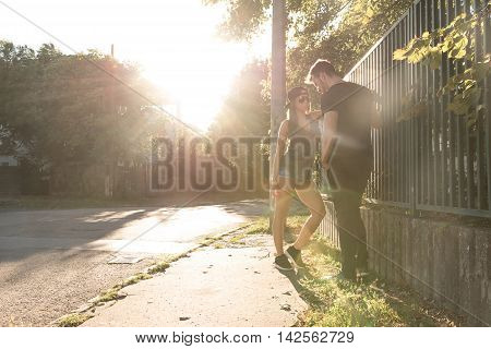 A young HipHop styled couple standing next to a fence during sunset in a urban environment.