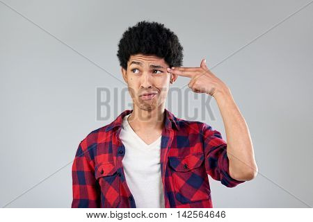 Funny man comedian frowning killing himself with imaginary gun, exasperated bored facial expression