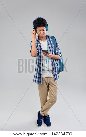 Happy smiling mixed race man choosing a song playlist on his mobile cell phone
