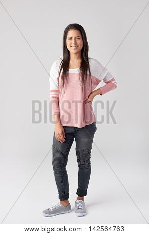 Full length portrait of pretty young woman in casual attire, isolated on grey in studio
