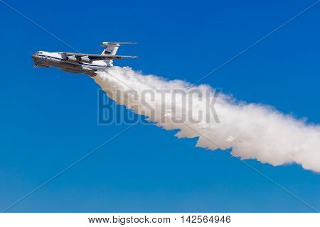 August 6 2016. Ryazan Russia. The aircraft of the Military Air forces of Russia perform aerobatics at an Airshow. The aircraft puts out the fire releasing water. Documentary Editorial Image.