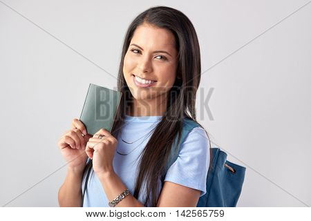 Happy mixed race tourist woman holding passport in studio, isolated on grey