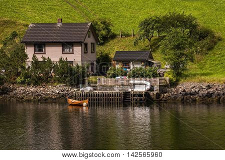 Amazing view of natural wonders mountains fjords and forests. Colors seem very beautiful. A small boat in front of small cute house. Reflections of the house and boat can seen on sea. Flam Norway