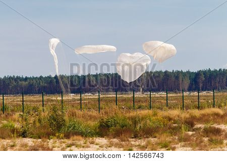 Military cargo parachute lands on the ground.