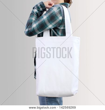 Girl is holding white blank cotton tote bag design mockup. Handmade shopping bag for girls.