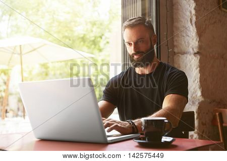 Handsome Bearded Businessman Wearing Black Tshirt Working Laptop Wood Table Urban Cafe.Young Manager Work Notebook Modern Interior Design Place.Coworking Process Business Startup.Blurred Background