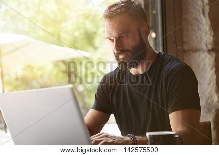 Concentrated Bearded Man Wearing Black Tshirt Working Laptop Wood Table Urban Cafe.Young Manager Work Notebook Modern Interior Design Loft Place.Coworking Process Business Startup.Blurred Background