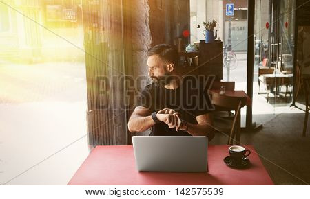 Young Bearded Businessman Wearing Black Tshirt Working Laptop Urban Cafe.Man Sitting Wood Table Cup Coffee Looking Through Window Touch Smartwatch.Coworking Process Business Startup Blurred Background
