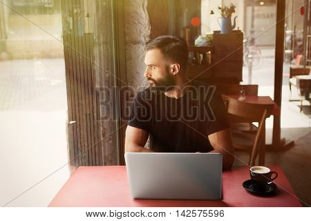 Young Bearded Businessman Wearing Black Tshirt Working Laptop Urban Cafe.Man Sitting Wood Table Cup Coffee Looking Through Window.Coworking Process Business Startup.Blurred Background.Sunlight effect