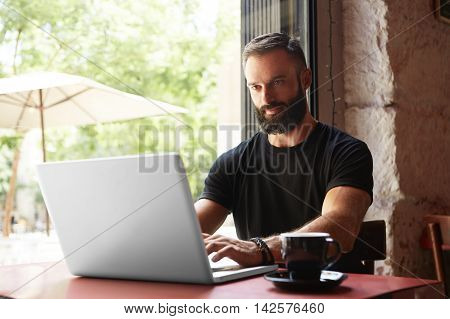 Handsome Bearded Businessman Wearing Black Tshirt Working Laptop Wood Table Urban Cafe.Young Manager Work Notebook Modern Interior Design Place.Coworking Process Business Startup.Color Filter