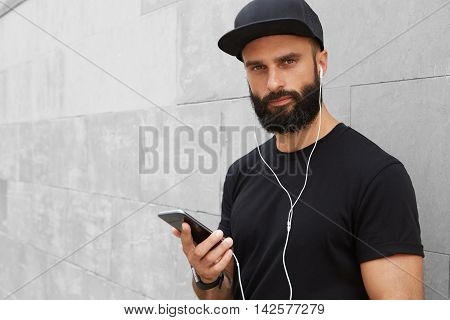 Bearded Muscular Man Wearing Black Tshirt Blank Snapback Cap Summer Time.Young Men Smiling Opposite Empty Gray Concrete Wall Background Using Smartphone Headphones.Horizontal Mockup.Color filter