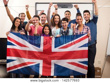 Exited British students with raised fists present their team with flag