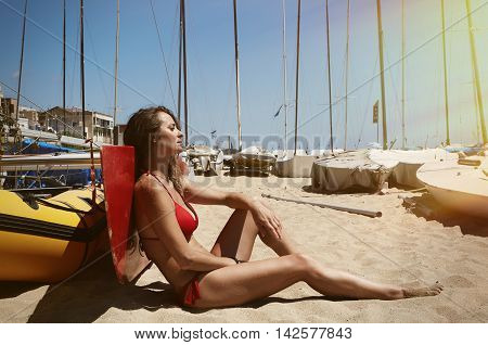 Photo Young Girl Making Chill Time Beach.Fitness Active Woman Spending Relax After Yaht Session Open Sea.Summer Season Race. Horizontal Picture. Boats Background. Sunlight effect