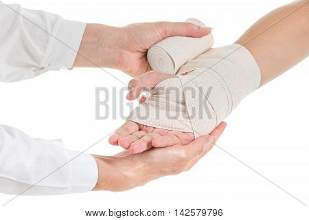 Doctor imposes an elastic compression bandage to the patient's wrist with injury to the ligaments isolated on white