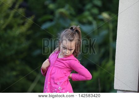 outdoor portrait of a little girl with pony tail dressed in pink shirt making angry or disappointed face