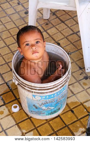 Asuncion, Paraguay - December 26: Unidentified Boy Sits In A Bucket With Water On December 26, 2014