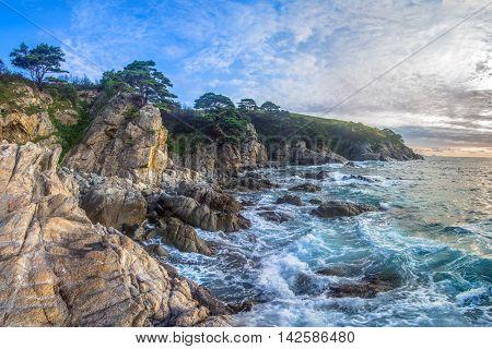Storm on the rocky sea coast at dawn