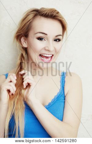 Hairstyle. Portrait of blond woman teenage girl plaiting braid hair. Indoor.