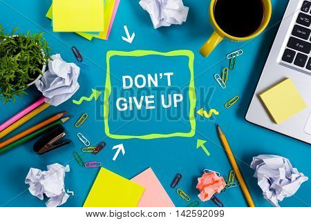 Don't give up. Office table with notepad, computer and coffee cup on blue background. Business creative consept top view