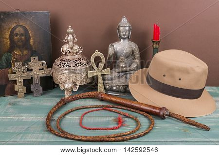 Adventure and archeological concept for lost artifacts with hat, whip, ancient iron vase, holy image, key of life, vintage crosses on green wood table and brown background.