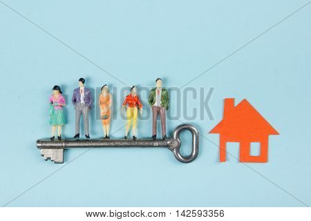 Real Estate concept. Construction building. People toy figures, paper model house with key on blue architect desk table background. Top view. Copy space for ad text
