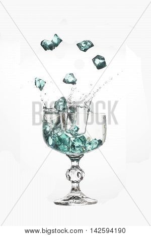 Falling ice cubes in water splashes in glas on white background.