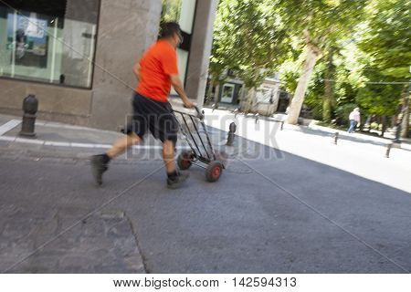 Mature running delivery man carrying a hand truck on city center street. Slow motion shot