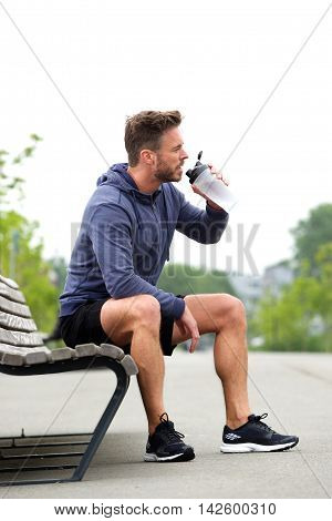 Athletic Man Sitting On Bench Drinking Water